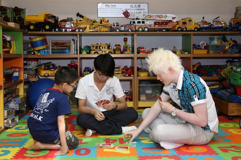 三名視障青少年在玩具閣玩桌上遊戲