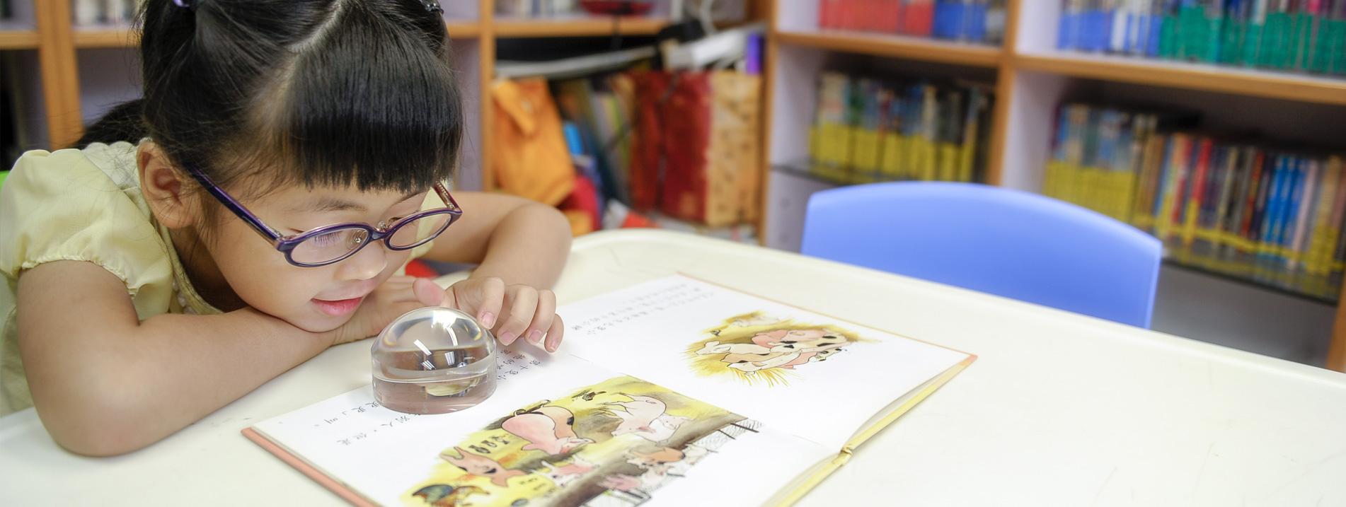一位視障小朋友用放大鏡閱讀