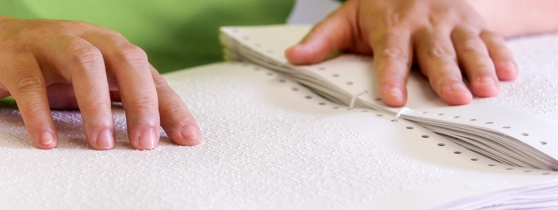 A hand touching braille