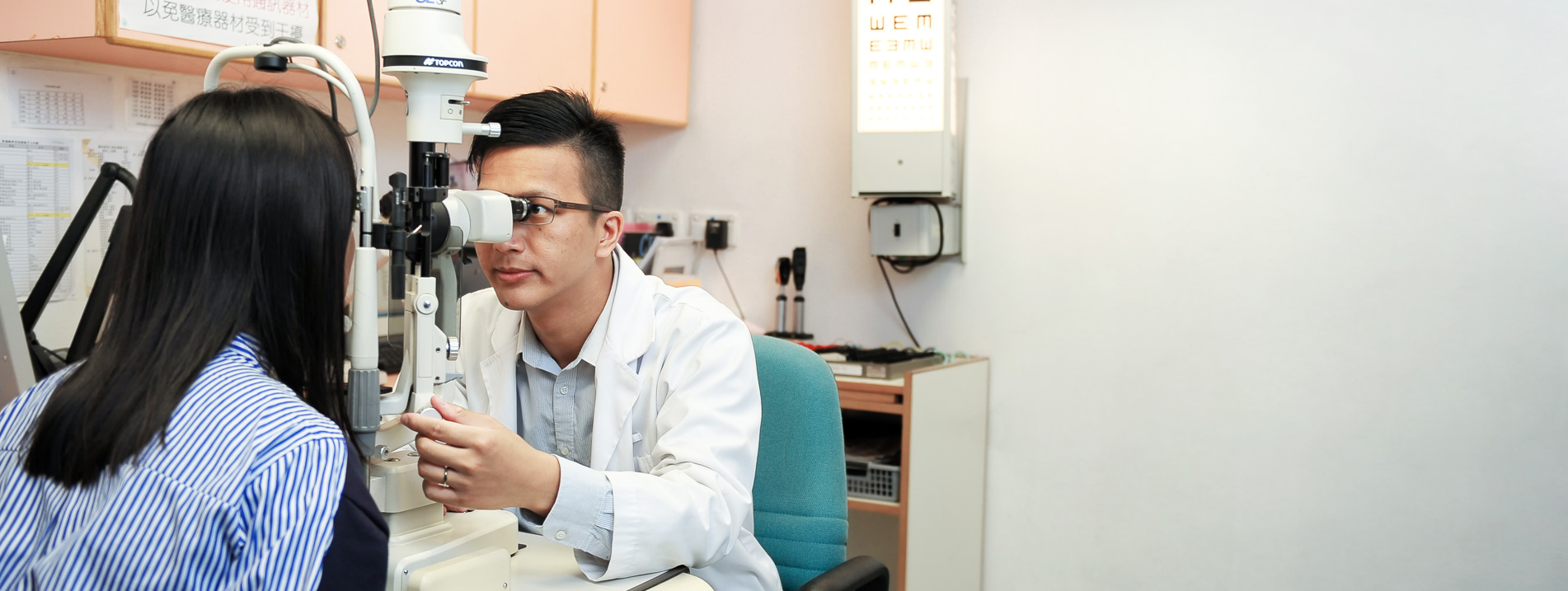 An optometrist conduct vision screening for a patient