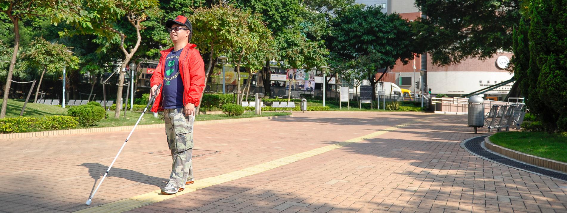 一位視障人士手持白杖獨立行走